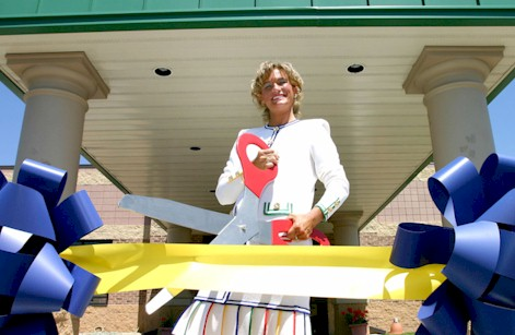 Kimberly Baeth cuts ceremonial ribbon with giant scissors
